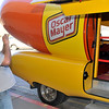 Jeff Freeman takes a picture of his son, Blake, on the steps of the Oscar Meyer Wienermobile Thursday at Jumbo's West. (Staff Photo by BILLY HEFTON)
