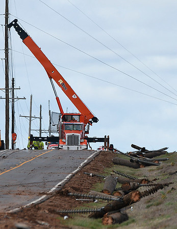 Crews from OG&E work to repair down power lines along Hwy 74 north of Covington Wednesday March 29, 2017. (Billy Hefton / Enid News & Eagle)