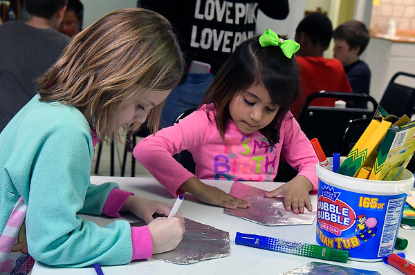 Aniston Hale and Natalie Mendoza decorate their faith shield in art club during after school activities at Zoe Bible Church Friday March 3, 2017. (Billy Hefton / Enid News & Eagle)