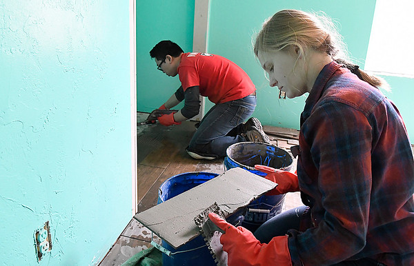 Marquette University students, Julia Walsh and Ken Banting, instal new tiles at a house being remodeled by Habitat For Humanity Tuesday March 14, 2017. (Billy Hefton / Enid News & Eagle)