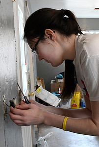 Marquette University student, Margaret Riley, installs a new outlet at a house being remodeled by Habitat For Humanity Tuesday March 14, 2017. (Billy Hefton / Enid News & Eagle)