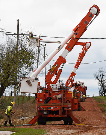 Crews from OG&E work to repair down power lines at the intersection of Longhorn Road and 186th Street northwest of Covington Wednesday March 29, 2017. (Billy Hefton / Enid News & Eagle)