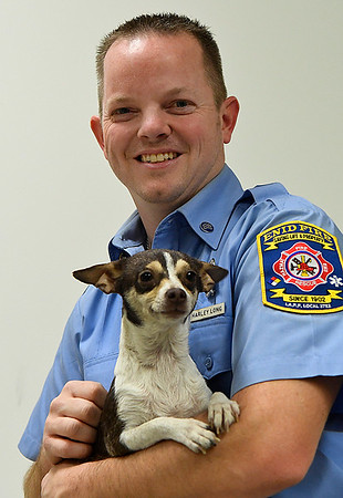 In this March 2, 2017 photo, Enid firefighter, Harley Long, holds the dog he revived during a house fire in November 2016. (Billy Hefton / Enid News & Eagle)