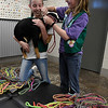 Kenzie Stotts holds a dog as Caitlyn Stotts attaches one the 100 leashes the Girl Scouts made for Enid Animal Control. (Billy Hefton / Enid News & Eagle)