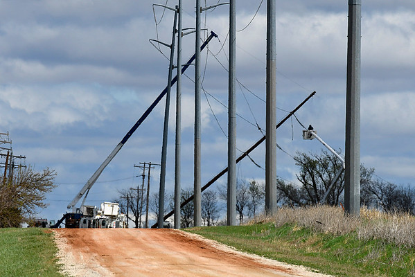 Crews work to repair down power lines near the intersection of Hwy 74 and Longhorn Road north of Covington Wednesday March 29, 2017. (Billy Hefton / Enid News & Eagle)
