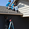 Marquette University students, Kelsiee Arreguin, Ben Lucarelli and Ali Piccininni, paint a house for Habitat for Humanity Wednesday March 14, 2018. (Billy Hefton / Enid News & Eagle)