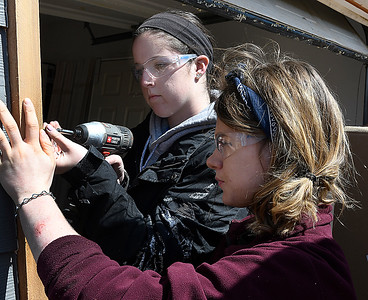 Marquette University students, Sarah Knoerr and Katelyn Dausman, install a garage door frame at a Habitat for Humanity house Wednesday March 14, 2018. (Billy Hefton / Enid News & Eagle)