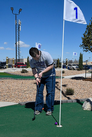 Jake Whinery sinks the first putt on the new miniature golf course at 4RKids following a ribbon cutting ceremony Friday March 16, 2018. (Billy Hefton / Enid News & Eagle)