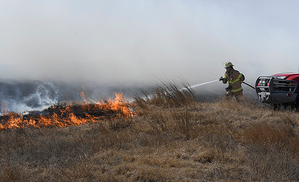 A Enid firefighter sprays water on flames of a grass fire along north 30th street Monday March 5, 2018. (Billy Hefton / Enid News & Eagle)