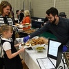 Ryan Costello serves food to Morilee Forbeck from Costello's Continental Cuisine during the Rotary Club's Festival of Flavor Tuesday March 6, 2018 at Prairie View Elementary. (Billy Hefton / Enid News & Eagle)