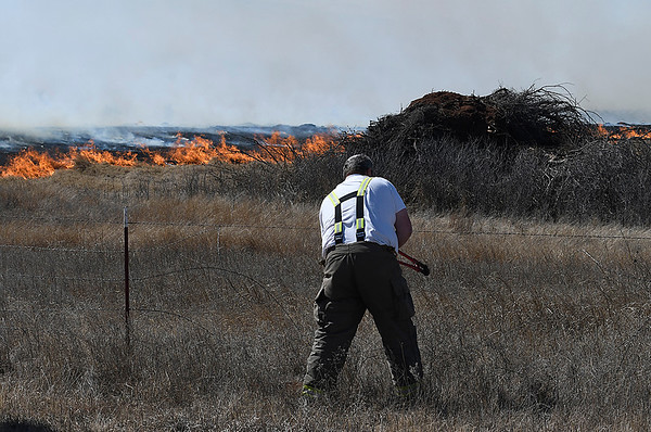 A firefighter cuts a fence north 30th street to gain acess to a grass fire Monday March 5, 2018. (Billy Hefton / Enid News & Eagle)