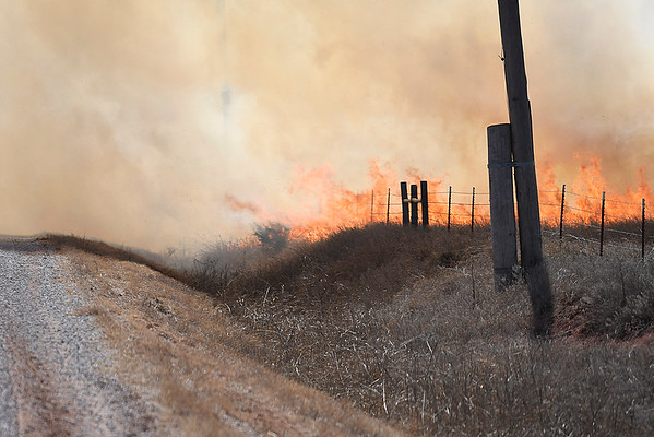 Wind driven flames of a grass fire approaches north 30th street Monday March 5, 2018. (Billy Hefton / Enid News & Eagle)
