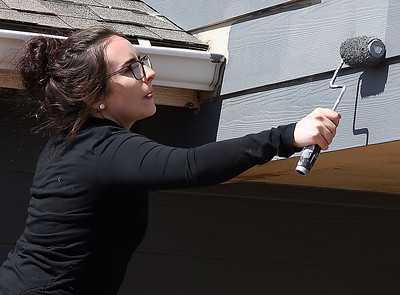Marquette University student, Kelsiee Arreguin, paints a house for Habitat for Humanity Wednesday March 14, 2018. (Billy Hefton / Enid News & Eagle)