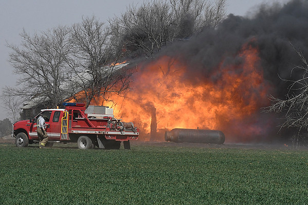 Vacant house on north 114th street burns Tuesday March 6, 2018. The structure caught fire when a grass fire jumped the road. (Billy Hefton / Enid News & Eagle)