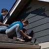 Marquette University students, Ben Lucarelli and Ali Piccininni, paint a house for Habitat for Humanity Wednesday March 14, 2018. (Billy Hefton / Enid News & Eagle)