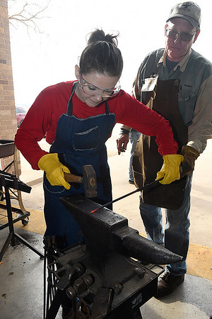 Jim Carothers watches as Sarah Hardaway works a piece of steel during a blacksmith class at Autry Technology Center Saturday March 10, 2018. (Billy Hefton / Enid News & Eagle)