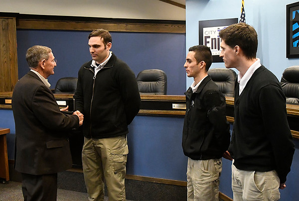 Enid mayor, Bill Shewey, presents badges to new police officers Gregory Schaer, Diego Gutierrez and Tanner Blachard, during a ceremony at city hall Thursday March 8, 2018. (Billy Hefton / Enid News & Eagle)