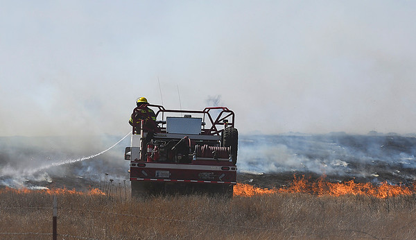 A brush unit from Hillsdale-Carrier sprays water on flames of a grass fire along north 30th street Monday March 5, 2018. (Billy Hefton / Enid News & Eagle)