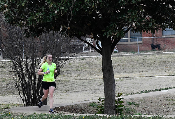 Jessica Brown passes a magnolia tree as she exercises at Meadowlake Park Monday March 26, 2018. (Billy Hefton / Enid News & Eagle)