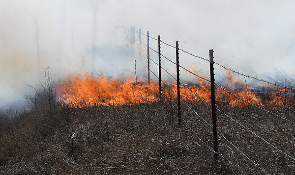 Wind driven flames of a grass fire crosses a fence line north 30th street Monday March 5, 2018. (Billy Hefton / Enid News & Eagle)