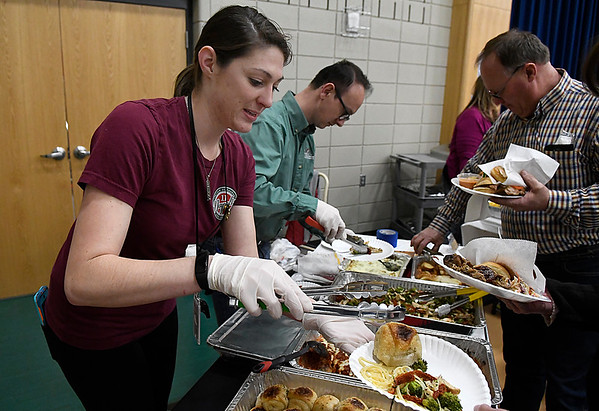 Trisha Tapp and Tony Zakuti serve items from Land Run Steakhouse during the Rotary Club's Festival of Flavor Tuesday March 6, 2018 at Prairie View Elementary. (Billy Hefton / Enid News & Eagle)