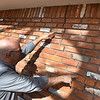Mike Honigsberg, Garfield County emergency management director, points out the crack caused by Sunday's earthquake at a house in Breckenridge. (Billy Hefton / Enid News & Eagle)