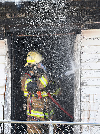 An Enid firefighter sprays a window sill while working a house fire in the 600 block of north 6th street Monday March 18, 2019. (Billy Hefton / Enid News & Eagle)