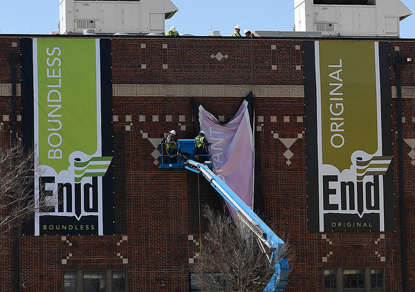 City employees work to replace the banners on the eastside of Conventikon Hall Monday March 18, 2019. (Billy Hefton / Enid News & Eagle)