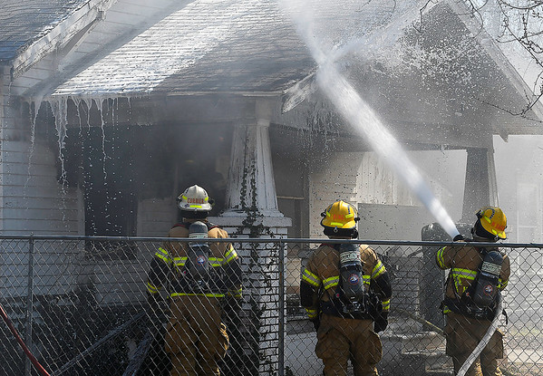 Enid firefighters work a house fire in the 600 block of north 6th street Monday March 18, 2019. (Billy Hefton / Enid News & Eagle)