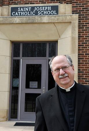Fr. Mark Mason stands outside St. Joseph Catholic School following an interview at St. Francis Xavier Catholic Church Friday March 22, 2019. (Billy Hefton / Enid News & Eagle)