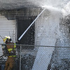 An Enid firefighter works a house fire in the 600 block of north 6th street Monday March 18, 2019. (Billy Hefton / Enid News & Eagle)