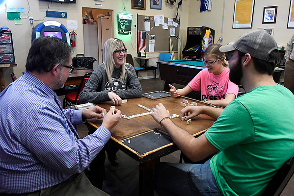 (left to right) Justin Lamunyon, Valerie Franek, Brooklyn Owens and Braxton Lamunyon play a hand of dominos at Dopey's Grill & Bar Wednesday March 20, 2019. (Billy Hefton / Enid News & Eagle)