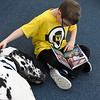 "Jacob Goldstein, 7, pets ""Doc"", a Harllequin Great Dane, as he reads at the Public Library of Enid and Garfield County Wednesday March 6, 2019. (Billy Hefton / Enid News & Eagle)"