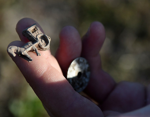 Rowdy Coffee shows an U.S. Mail pin he found metal detectingTuesday, March 10, 2020. (Billy Hefton / Enid News & Eagle)