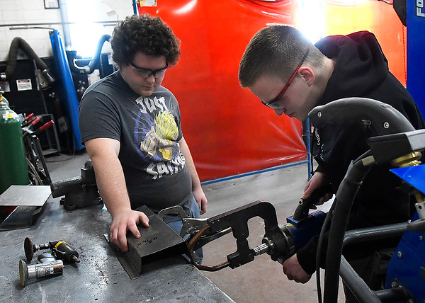 Gavin Wall hold  apart in place as Dylan Johnson uses a spot welder in the collision repair shop at Autry Technology Center. (Billy Hefton / Enid News & Eagle)