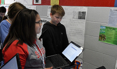 Chisholm Middle School 6th graders, Ben Athinson and Makalynn Cole, use chrome books to complete assignments for geography class. (Billy Hefton / Enid News & Eagle)