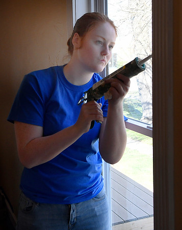 Marquette University student, Katie Robertson, kaulks a window while working for Habitat for Humanity Tuesday, March 10, 2020. (Billy Hefton / Enid News & Eagle)