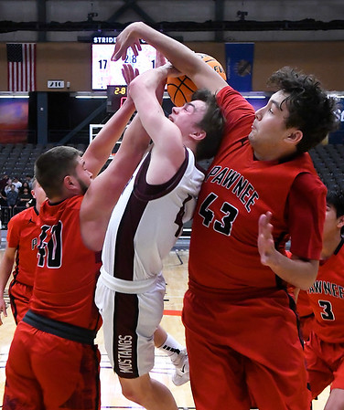 Pioneer's Ty Dennett is fouled as he goes up against Pawnee's Kamden Jones and Buchanan during the Area 1 tournament at Stride Bank Center Thursday, March 5, 2020. (Billy Hefton / Enid News & Eagle)