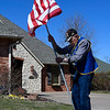 Pastor Kenneth Wade places an American flag in the yard in Waterford Court. (Billy Hefton / Enid News & Eagle)
