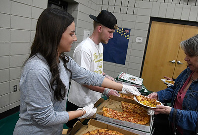 Maggie Swann and Jack Fossett serves pizza from Papa John's during Rotary's Festival of Flavor Tuesday, March 10, 2020 at Prairie View Elementary. (Billy Hefton / Enid News & Eagle)
