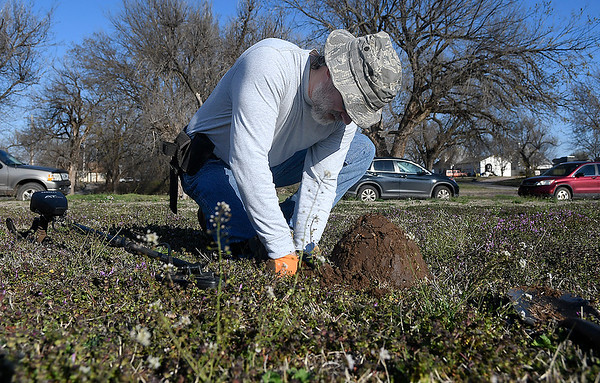 James Popham uses his hands to sift through the dirt while metal detecting Tuesday, March 10, 2020. (Billy Hefton / Enid News & Eagle)