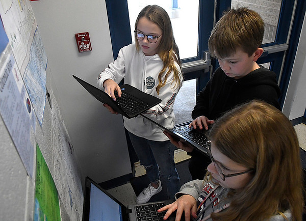 Chisholm Middle School 6th graders, Skylar Crabtree, Ben Athinson and Morgan Crenshaw, use chrome books to complete assignments for geography class. (Billy Hefton / Enid News & Eagle)