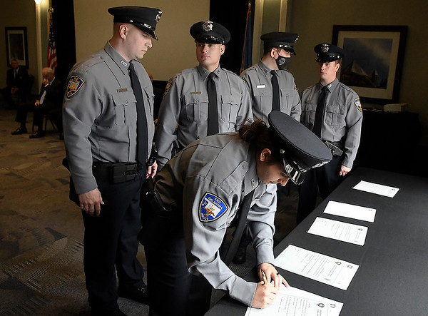 Ashley Milton signs her Oath of Office as fellow graduates Jeran Jones, Cody Jones, Cameron Thomas and Jason Guth look on following their swearing-in Thursday, March 11, 2021 at the Stride Bank Center. The new officers are the first graduates of the Enid Police Academy. (Billy Hefton / Enid News & Eagle)