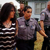 Enid Police officers (right) escort a woman to a waiting police vehicle after arresting her during a large-scale drug raid early Thursday, May 8, 2014. Oklahoma Bureau of Narcotics, Oklahoma Highway Patrol, State Police, Enid Police Department and Garfield County Sheriff Department were among the agencies involved in the sweep. (Staff Photo by BONNIE VCULEK)