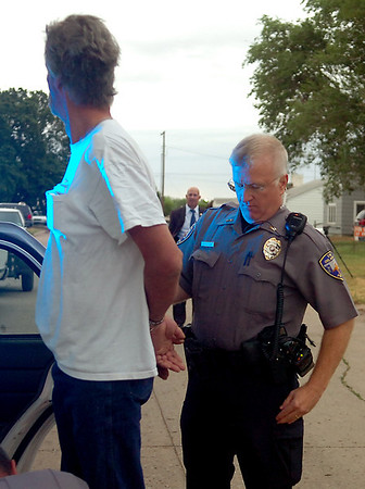 Enid Police officer Eric Holtzclaw arrests Jack Roland during the large-scale drug sweep by the Oklahoma Bureau of Narcotics, Oklahoma Highway Patrol, Enid Police Department, Garfield County Sheriff Department and other law enforcement agencies across the state. (Staff Photo by BONNIE VCULEK)