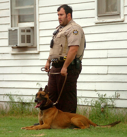 A Garfield County Sheriff Deputy stands near his K-9 during the early morning drug sweep in Enid Thursday, May 8, 2014. (Staff Photo by BONNIE VCULEK)