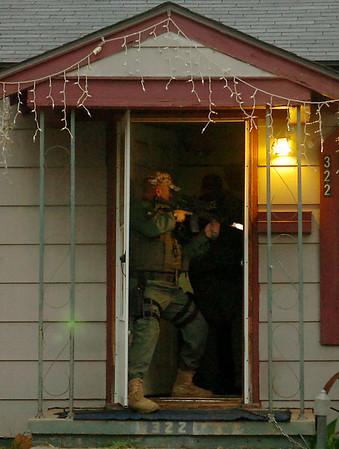 A State Police officer stands in the doorway of an Enid residence where two men were arrested during a large-scale drug sweep Thursday, May 8, 2014. (Staff Photo by BONNIE VCULEK)