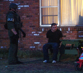A State Police officer (left) guards a man (center) who was arrested during an early morning drug sweep in Enid Thursday, May 8, 2014. Two children, a young girl and boy, were removed from the home. (Staff Photo by BONNIE VCULEK)