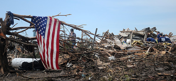 An American flag drapes a fallen tree (left) as firefighters (right) help one of their own salvage personal items from his home in Westmoor Tuesday, May 21, 2013, after a massive tornado devastated the community of Moore, Okla. Monday afternoon, leaving 24 dead, including 9 children. (Staff Photo by BONNIE VCULEK)