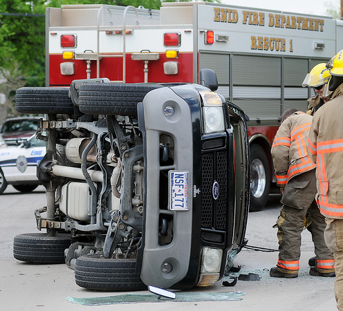 Enid firefighters assist at the scene of a roll-over accident at 624 S. Independence as Enid Police officers investigate the two-vehicle crash Friday, May 10, 2013. (Staff Photo by BONNIE VCULEK)